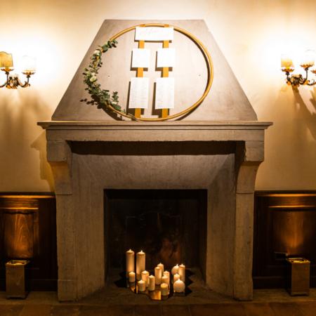 camino con candele accese appoggiate su un pavimento di specchi dorati