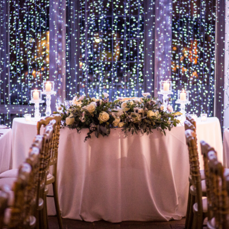 tavolo degli sposi con sullo sfondo una parete di luci natalizie decorato con fiori bianchi e rami di pino