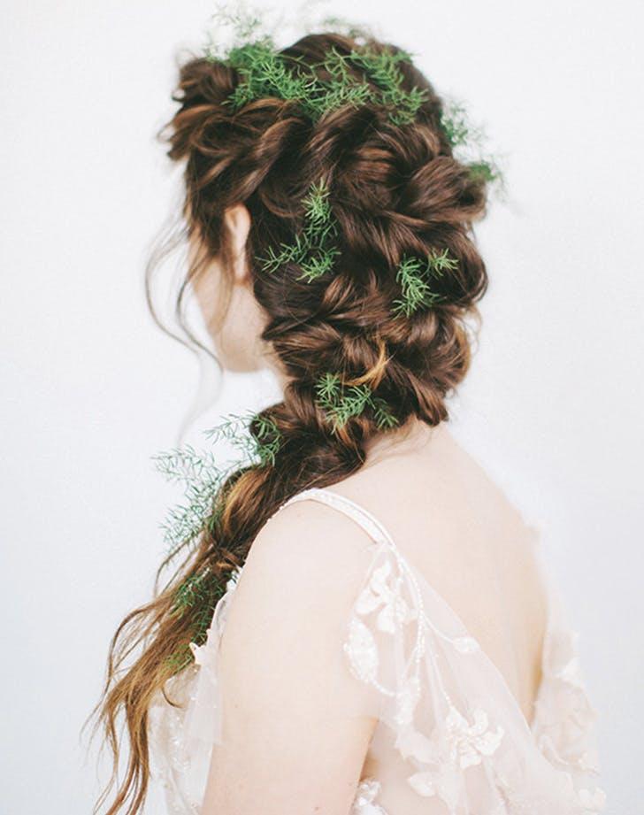 matrimonio invernale caperli sposadi schiena con capelli pettinati a treccia con inseriti all'interno alcuni rametti di conifera
